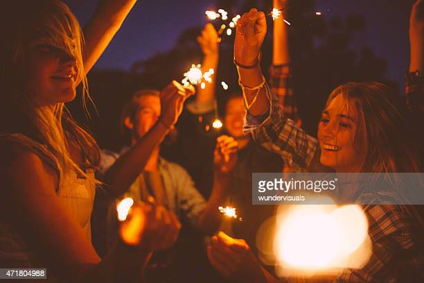 Teen friends dancing and celebrating with sparklers at night