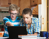 Two male teen friends in kitchen with books and laptop