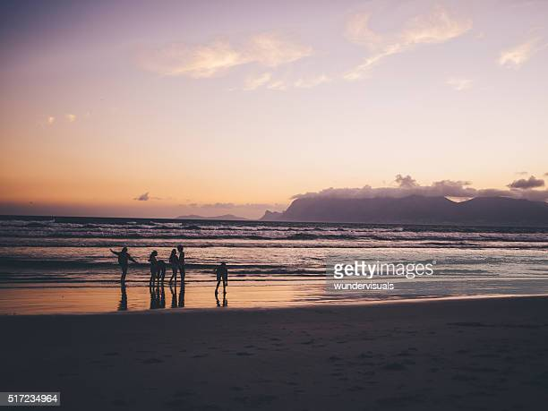 Teen friends enjoying a walk at beach on sunset