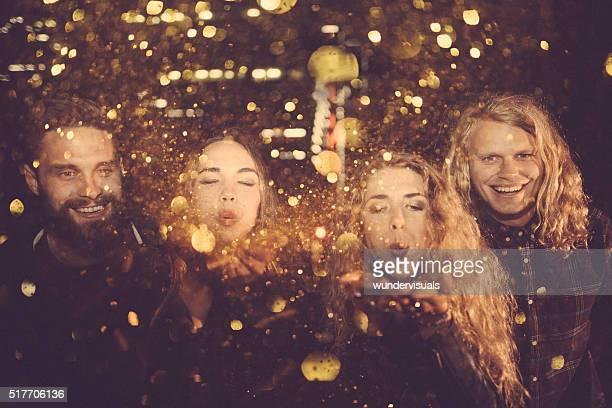 Les jeunes amis fête doré avec des confettis de nuit