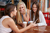 beautiful young girls having coffee at outdoor cafe with mobile cell phone