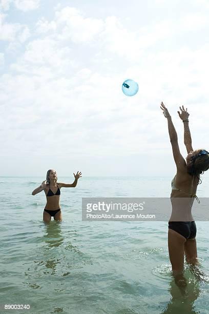 Teen friends waist deep in water playing with beach ball