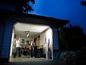 Teen garage band practicing at night in garage