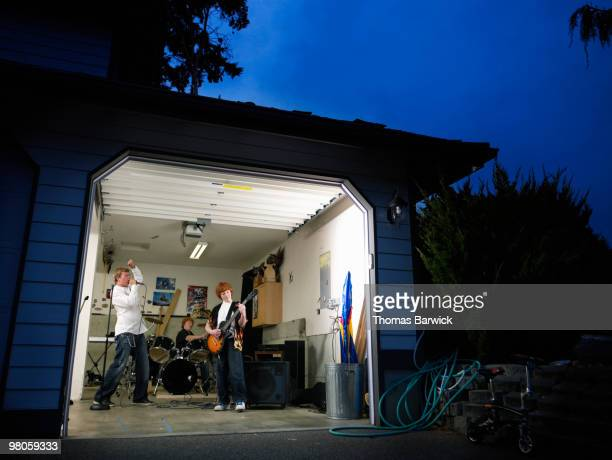 Teen garage band practicing at night in garage