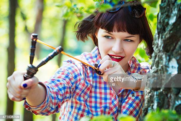 Teen girl aiming a slingshot in the woods