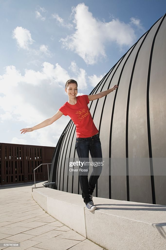 Teen girl balancing on barrier : Stock Photo