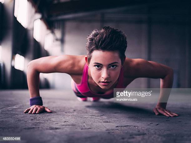 Teen girl doing push ups on a concrete floor