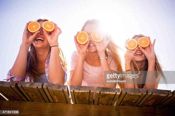 Teen girl friends holding up oranges for eyes