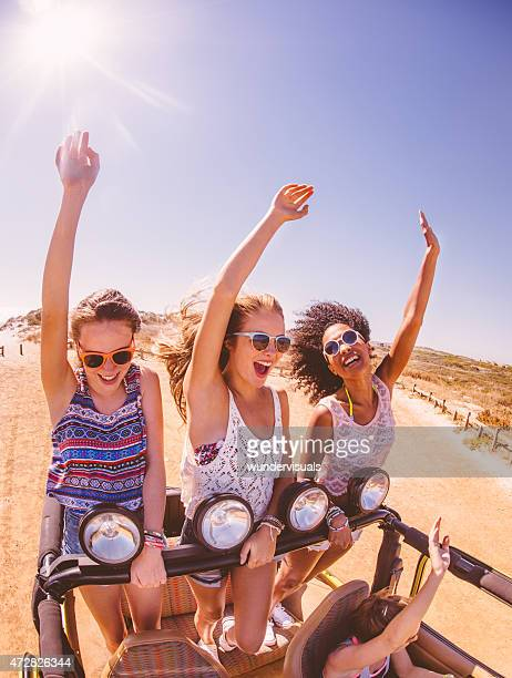 Teen girl friends in back of vehicle on road trip