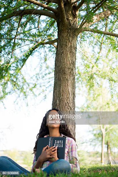 Teen girl holding Bible with eyes closed