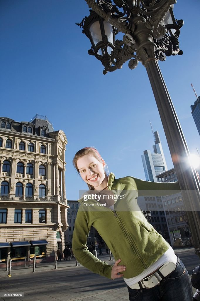 Teen girl holding lamppost : Stock-Foto