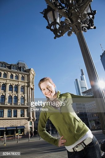 Teen girl holding lamppost : Stockfoto