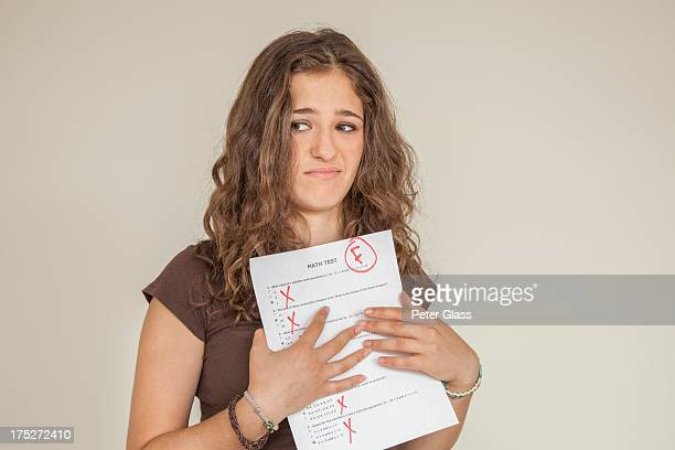 Teen girl holding math test with a grade of 'F'