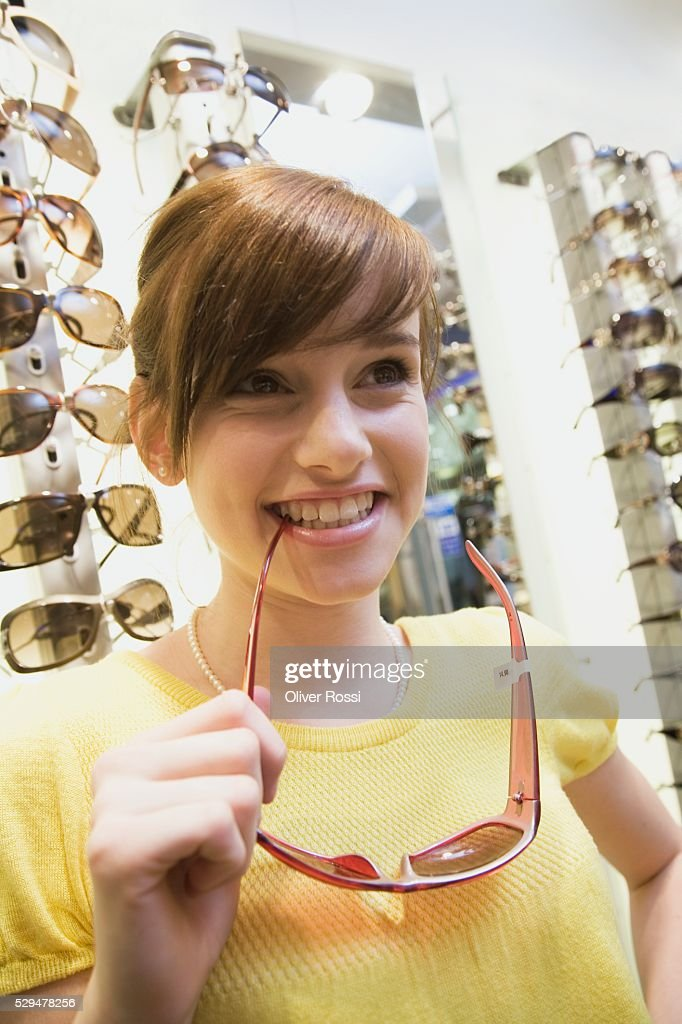 Teen girl holding sunglasses in store : Stock Photo