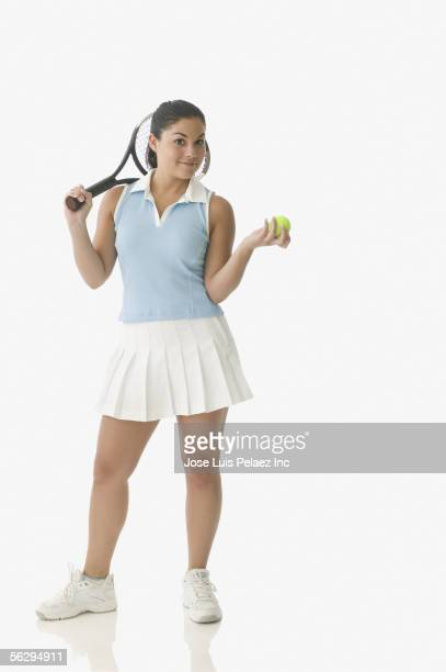 Teen girl holding tennis racket and ball