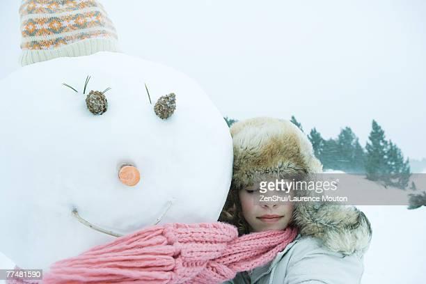 Teen girl hugging snowman