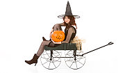 Portrait of Latina teenager girl in black Halloween costume (fishnet dress) sitting on farm cart in straw with carved pumpkin (Jack O' Lantern) on the floor