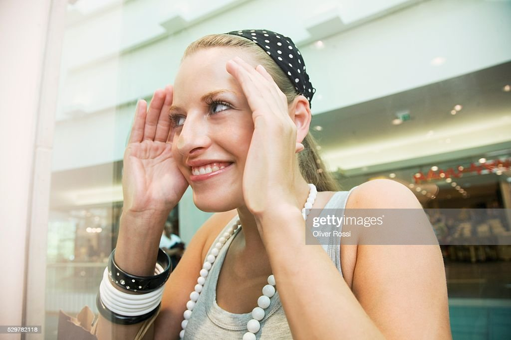 Teen girl in shopping center looking through window : Stock-Foto
