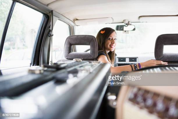 Teen girl in vehicle with amplifier and guitar cases
