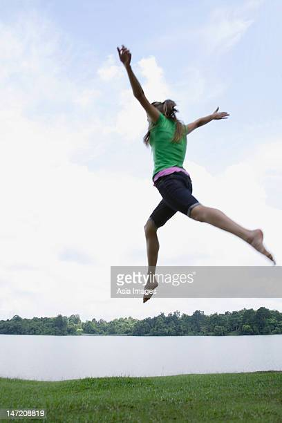 Teen girl jumping by lake
