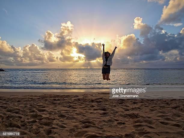 Teen girl jumping on Waikiki Beach with sun rays shooting through clouds