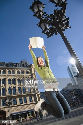 Teen girl jumping with sign : Stock Photo
