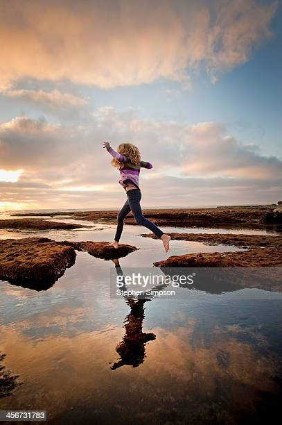 teen girl leaping over tide pools