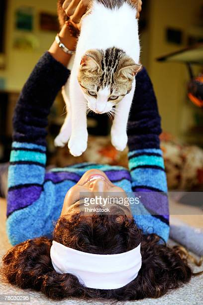 A teen girl lies on her back holding her cat above her.