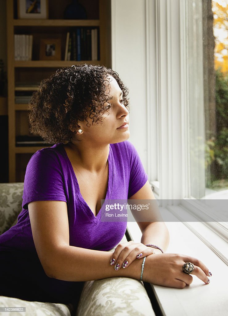Teen girl looking out the window : Stock Photo