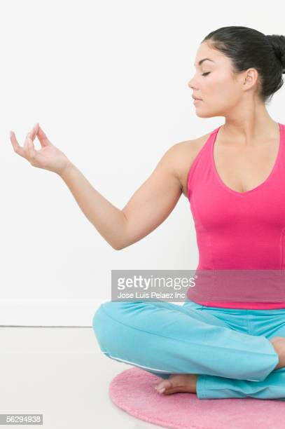Teen girl meditating on floor mat