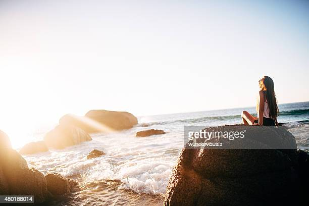Teen girl on rocks at beach on tranquil summer afternoon