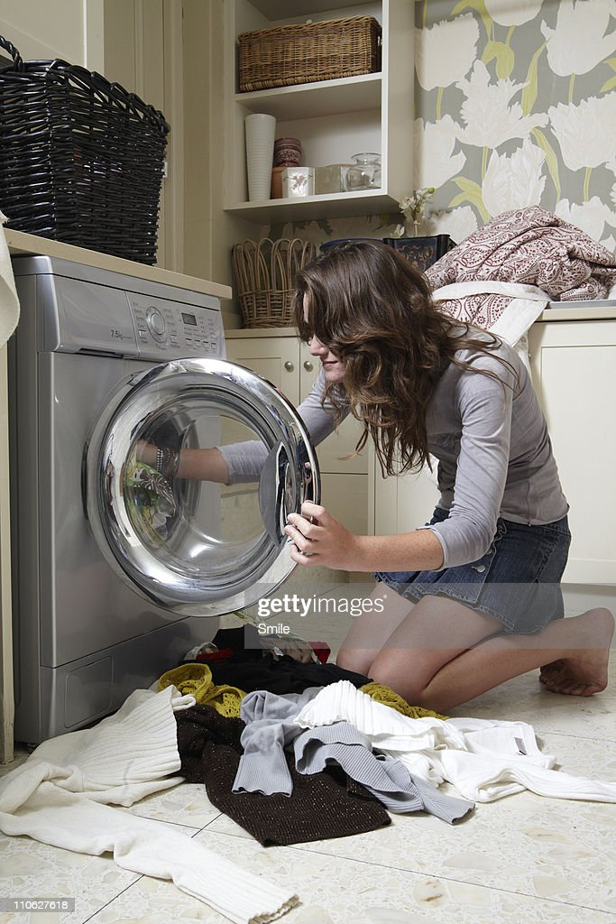 Teen girl packing washing into machine : Stock Photo