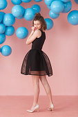 teen girl posing on pink wall and blue balloons backdrop. Vertical full-lenght portrait rear view.