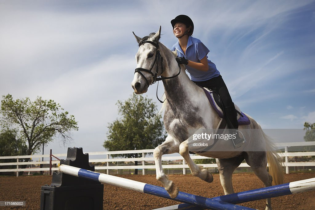 Teen Girl Riding Horse Over Jump