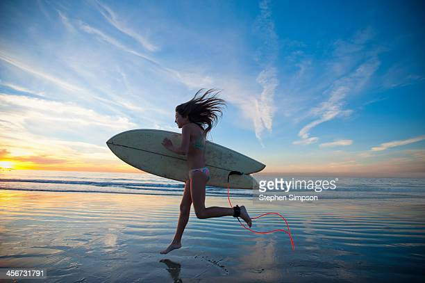 teen girl running [leaping] to the surf