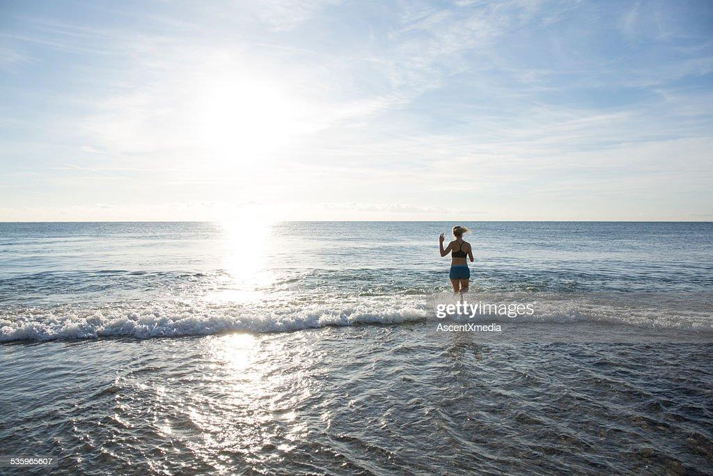 Teen girl runs across beach into waves, gentle surf : Stock Photo