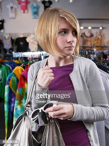 Teen girl shoplifting sunglasses