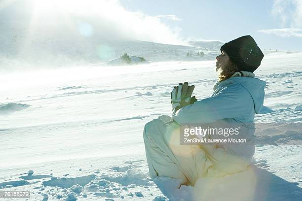 Teen girl sitting in snow with hands clasped and eyes closed
