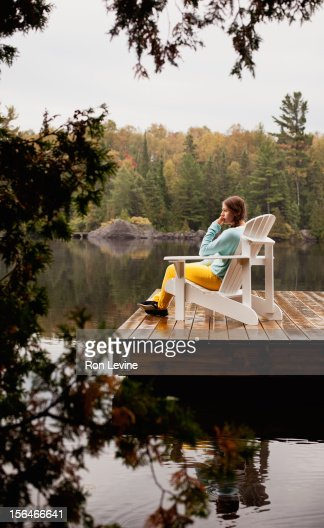 Teen girl sitting on a dock chair, deep in thought : Stock Photo