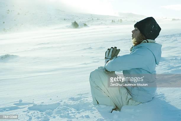 Teen girl sitting on snow in prayer position