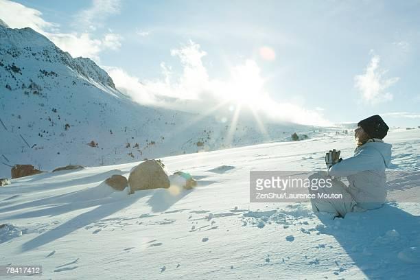 Teen girl sitting on snow in prayer position, sun shining over edge of mountain