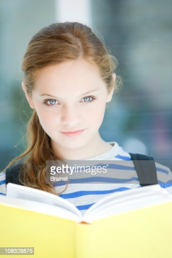 Teen Girl Smiling Looking At Camera Holding Book Stock