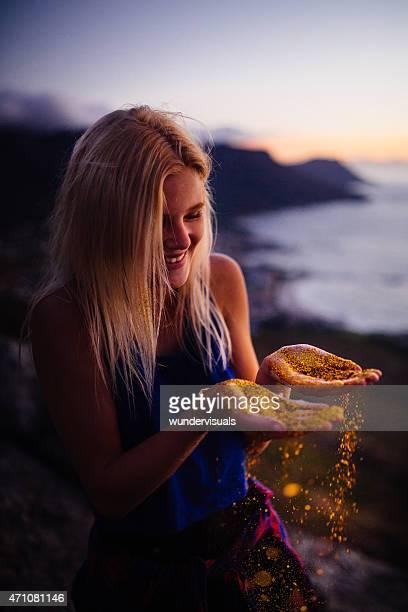 Teen Mädchen lächelnd mit glitter fallen Ihre Hände
