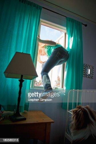 teen girl sneaking out her bedroom window : Stock Photo