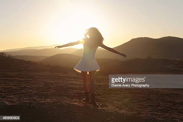 Teen girl spinning in field at sunset