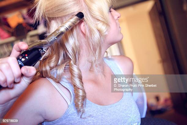 Teen Girl Styling Hair With Curling Iron