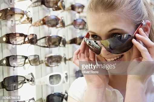 Teen girl trying on sunglasses : Bildbanksbilder