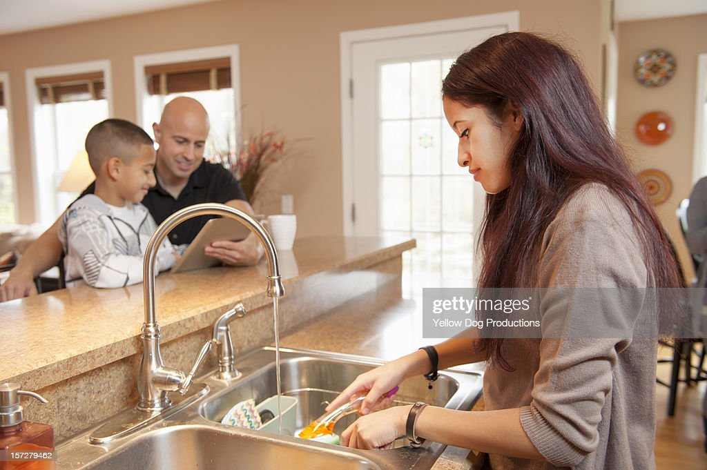Teen Girl washing dishes at home : Stock Photo