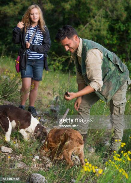 Teen girl watches the hunter collect a truffle that his dogs sniffed and dug out, Abruzzo, Italy, Europe