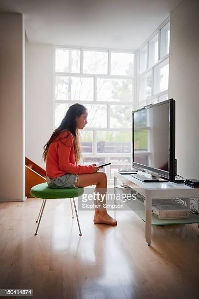 teen girl watching large flat screen TV